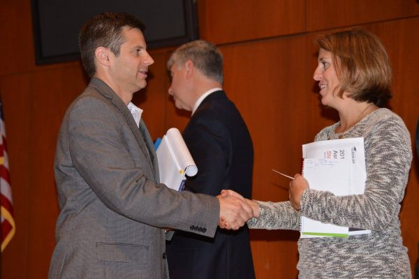 Casey Cobb shaking hands with woman at CEPA event